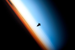 Space Shuttle Endeavour orbiting in the thermosphere. Because of the angle of the photo, it appears to straddle the stratosphere and mesosphere that actually lie more than 250 km (160 mi) below. The orange layer is the troposphere, which gives way to the whitish stratosphere and then the blue mesosphere.[28]