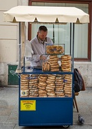 A street vendor in Kraków, Poland, selling pretzels (labeled precle in Polish), as well as obwarzanki krakowskie and bagels