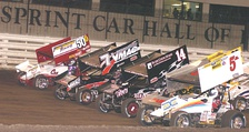 A World of Outlaws sprint car race; a pair of cars have numbers with a trailing letter.