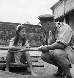"Rangoon, Burma. August 8, 1945. A young ethnic Chinese woman from one of the Imperial Japanese Army's ""comfort battalions"" is interviewed by an Allied officer."