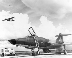 U.S. Air Force technicians prepare a McDonnell RF-101 Voodoo for a photo reconnaissance mission