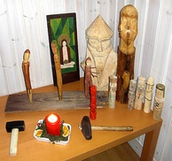 A wooden table indoors on which have been placed wooden icons