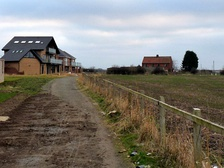 a path at the edge of The Rings housing with the Barwick House Farm site to the right
