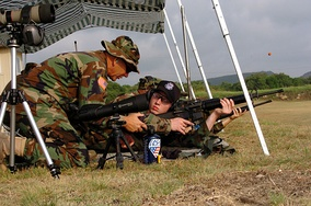 U.S. Army Reserve Sgt. Maj., left, instructs U.S. Navy Midshipman on proper body positioning during live-fire marksmanship training in June 2005.