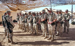 Air Force security forces from the 405th Air Expeditionary Wing listen to instruction during guard mount at an Operation Enduring Freedom location. A guard mount is conducted to brief security forces troops before a shift change.