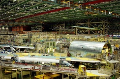 Airplane assembly hall, featuring heavy machinery. Large cylindrical airplane sections and wings are readied for mating with other major components. Above are the cranes which ferry heavy and outsize parts of the 747.