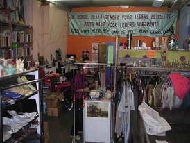 "Inside Utrecht Giveaway shop, where the banner reads: ""The earth has enough for everyone's need, but not for everyone's greed"""