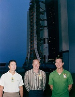 Three men stand in front of a rocket