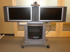 Dual display: An older Polycom VSX 7000 system and camera used for videoconferencing, with two displays for simultaneous broadcast from separate locations