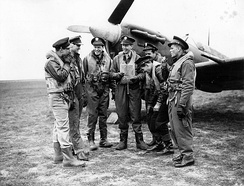 Former RAF Eagle Squadron pilots, now with the USAAF 4th Fighter Group sharing a smoke in front of a Spitfire at Debden
