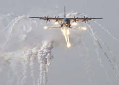 A British C-130J Hercules aircraft launches flare countermeasures before being the first coalition aircraft to land on the newly reopened military runway at Baghdad International Airport