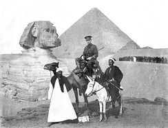 A soldier in uniform sitting on a camel posed in front of the Great Sphinx of Giza