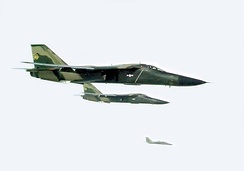 Two green jet aircraft flying together, right of wing. Further out in the background is another jet aircraft.