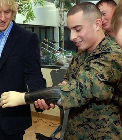 Actor Owen Wilson gripping the myoelectric prosthetic arm of a United States Marine