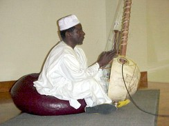 A Mandinka Griot Al-Haji Papa Susso performing songs from the oral tradition of the Gambia on the kora.