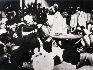 "Congress ""extremist"" Bal Gangadhar Tilak speaking in 1907 as the party split into the Moderates and the Extremists. Seated at the table is Aurobindo Ghosh and to his right is Lala Lajpat Rai, both allies of Tilak."