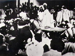 "Congress ""extremist"" Bal Gangadhar Tilak speaking in 1907 as the Party split into moderates and extremists. Seated at the table is Aurobindo Ghosh and to his right (in the chair) is G. S. Khaparde, both allies of Tilak."