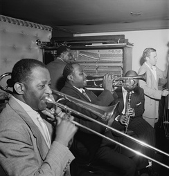Wilbur de Paris playing trombone in a jazz ensemble, c.1947
