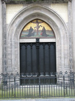 Two large black church doors with a crucifixion scene painted above with Luther and Melanchthon kneeling