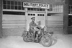 "An African-American Military Policeman on a motorcycle in front of the ""colored"" MP entrance during World War II."