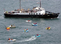 The Lundy ferry Oldenburg sails into Ilfracombe Harbour, North Devon, past inflatable ThunderCat powerboats waiting to begin an offshore race.