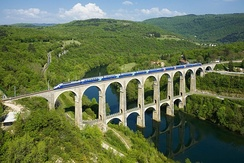 A TGV Duplex crossing the Cize–Bolozon viaduct. The train can reach a maximum speed of 360 kilometres per hour (220 mph).