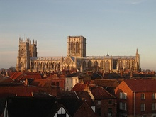 York Minster seen from the side – a long building with a pair of towers at one end and a massive central tower with two perpendicular windows. The round rose window can be seen on the south transept.
