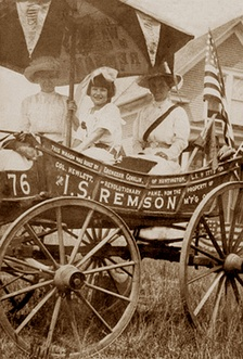 "Edna Kearns (left) with the horse-drawn suffrage wagon, the ""Spirit of 1776,"" on its maiden voyage from Manhattan to Long Island in July 1913. Also in wagon: Serena Kearns (center) and Irene Davison (right)."