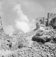 A Sherman tank of 19th Armoured Regiment, 4th New Zealand Armoured Brigade supporting infantry of 6th NZ Infantry Brigade, in a reconstruction of the action at Cassino, Italy, 8 April 1944.