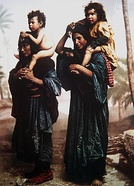 Bedouin mothers carrying their children on their shoulders. Color photo taken in the late 19th century by the French photographer Félix Bonfils.
