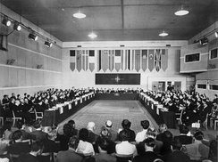 A long rectangular room with multiple rows of seated individuals on each side, and flags hanging at the far end.