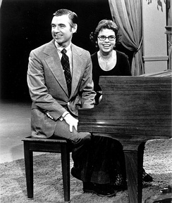 Fred and Joanne Rogers sitting at a piano.