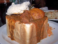 An example of bunny chow served in Durban, originated in the Indian South African community.[49]