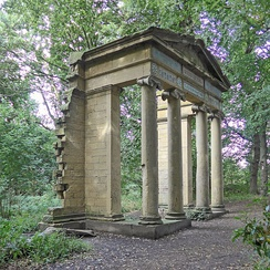 An arch with columns and a pediment standing alone in a woodland