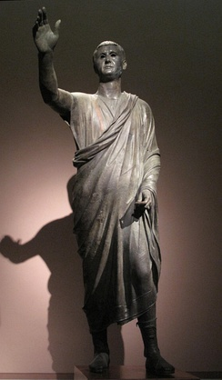 The Orator, c. 100 BCE, an Etrusco-Roman bronze sculpture depicting Aule Metele (Latin: Aulus Metellus), an Etruscan man wearing a Roman toga while engaged in rhetoric; the statue features an inscription in the Etruscan alphabet.