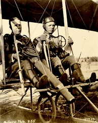Captain Charles Chandler (with prototype Lewis Gun) and Lt. Roy Kirtland in a Wright Model B Flyer after the first successful firing of a machine-gun from an aeroplane on June 7, 1912.[38]