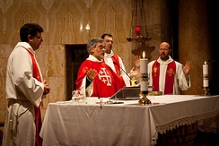 A contemporary Mass in modern practice. As versus populum became the common posture and gesture practised after the council. Note that the priest faces the congregation, while the vestments and religious artwork are less intense and ornate.