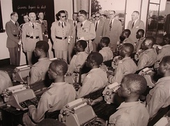 King Baudouin visits the school of the Force Publique in Luluabourg, 1955. The King is accompanied by His Excellency Léon Pétillon, Governor-General of the Belgian Congo.