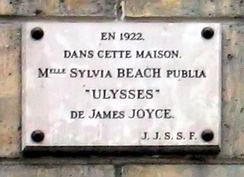 "Memorial plaque, at 12 Rue Odéon, Paris VI mentioning that "" In July 1920, Beach met Irish writer James Joyce at a dinner party hosted by French poet André Spire. Soon after, Joyce joined Beach's lending library.[6] Joyce had been trying, unsuccessfully, to publish his manuscript for his masterpiece, Ulysses and Beach, seeing his frustration, offered to publish it.[7] In 1922 Sylvia Beach published James Joyce's Ulysses in this apartment."""