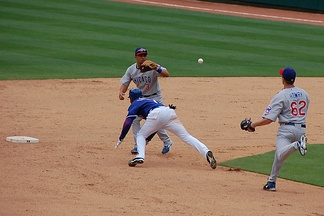A typical rundown situation in baseball showing a baserunner for the Texas Rangers as he attempts to evade the Chicago Cubs defense.