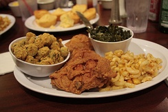 A traditional soul food dinner consisting of fried chicken with macaroni and cheese, collard greens, breaded fried okra and cornbread.