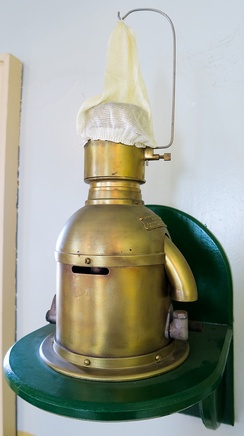"An 85mm Chance Brothers Incandescent Petroleum Vapour Installation which produced the light for the Sumburgh Head lighthouse until 1976. The lamp (made in approx. 1914) burned vaporized kerosene (paraffin); the vaporizer was heated by a denatured alcohol (methylated spirit) burner to light. When lit some of the vaporised fuel was diverted to a Bunsen burner to keep the vaporizer warm and the fuel in vapor form. The fuel was forced up to the lamp by air; the keepers had to pump the air container up every hour or so. This in turn pressurized the paraffin container to force the fuel to the lamp. The ""white sock"" is in fact an unburnt mantle on which the vapor burned."