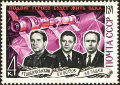 The Soyuz 11 crew with the Salyut station in the background, in a Soviet commemorative stamp