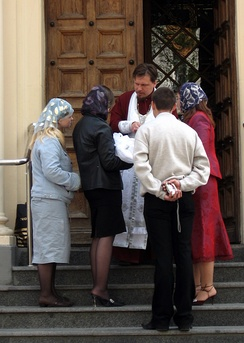 Russian Orthodox priest greeting an infant and its godparents on the steps of the church at the beginning of the Sacred Mystery of Baptism.
