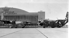 A C-123K Provider (731st Tactical Airlift Squadron) and a C-130B Hercules (337th Tactical Airlift Squadron) are in front of the Westover Air Force Base Hangar for a 1977 publicity photo.
