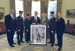 "White House photo of March 11, 2002, unveiling of ""Heroes"" stamp. From left: Postmaster General John E. Potter; Firefighters Billy Eisengrein and George Johnson; George W. Bush; Gary Ackerman; Firefighter Dan McWilliams; and Record photographer Thomas E. Franklin, who took the photo featured on the stamp."
