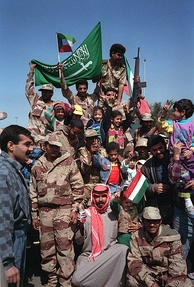 Civilians and coalition military forces wave Kuwaiti and Saudi Arabian flags as they celebrate the retreat of Iraqi forces from Kuwait.