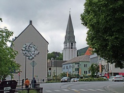 Molde's main street and commercial centre. Molde Cathedral (orange roof on far right) with its freestanding bell tower replaced the church that was destroyed during World War II