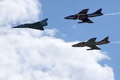 A pair of ex-Swiss Air Force Hunters flying in close formation behind a single Mirage III, 2011