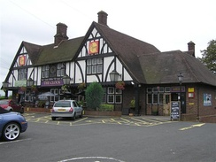 "The Clock, Birmingham — an example of a mock Tudor pub, now demolished to make way for the expansion of Birmingham Airport. Many were built between the world wars as part of the ""improved"" pub movement and as ""roadhouse"" inns—with large car parks to attract passing trade.[40]"